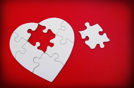 white puzzle shaped heart on red textured background
