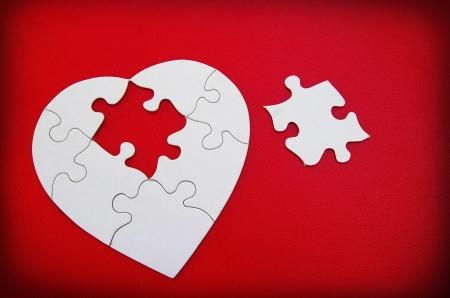 witte puzzel vormige hart op rode getextureerde achtergrond