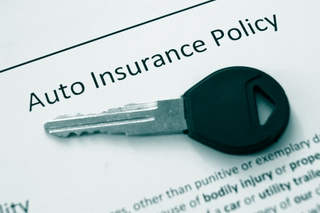 closeup of an auto insurance policy and car key photo