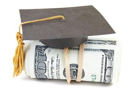 mini graduatie GLB op opgerold geld Stockfoto