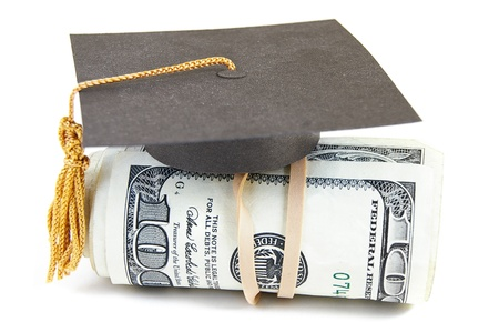 scholarship: mini graduation cap on rolled up cash
