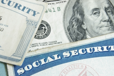 social security: social security cards and US money - retirement concept