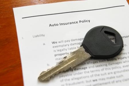 liability insurance: Closeup of a car key on an auto insurance policy