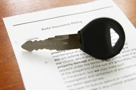 car key on an auto insurance policy photo