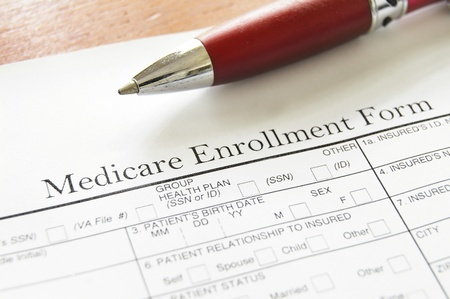 billing: Closeup of Medicare enrollment form and pen