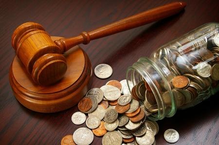 juridische hamer en muntstukken in een munt pot