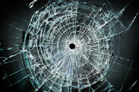 vidrio roto: Ventana rota con un agujero de bala en el medio