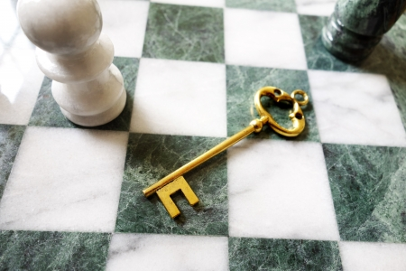 old gold key on a chess board