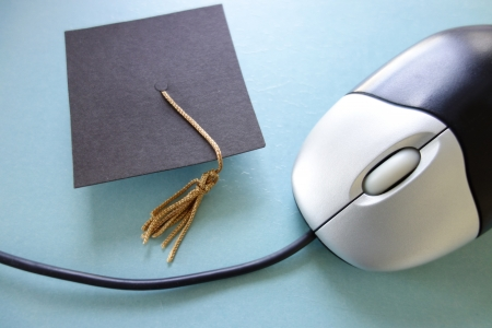 internet class: Closeup of a computer mouse and graduation cap - online education concept                               Stock Photo