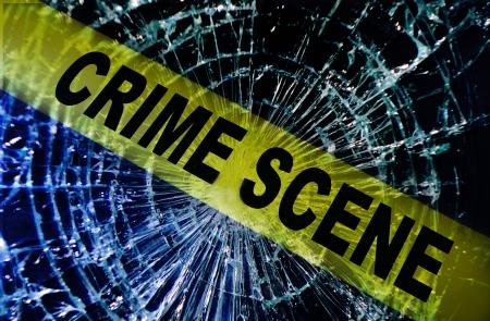 crimes: Broken window with yellow Crime Scene tape                               Stock Photo