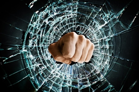 Fist punching thru a glass window                                Stock Photo - 17337645