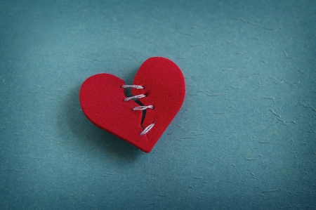 relationship breakup: red heart, broken with threaded stitches