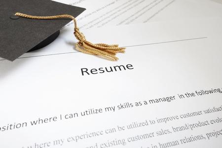 Mini graduation cap on a job hunters resume                                photo