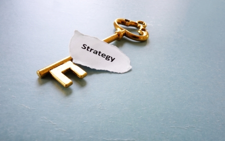 old key and Strategy text on paper scrap