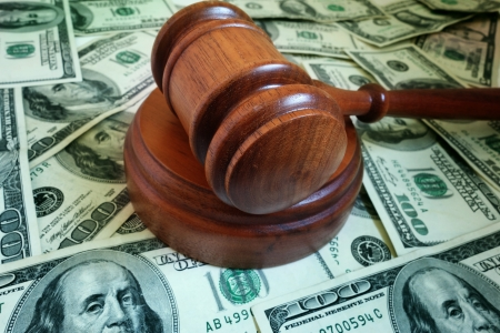 lawsuit: closeup of a legal gavel on US cash