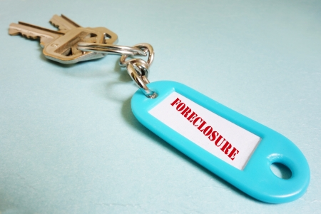 homeownership: Closeup of a keychain with red Foreclosure text