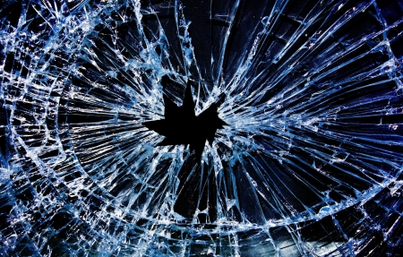 cracked glass: shattered glass with a hole in the middle                                Stock Photo