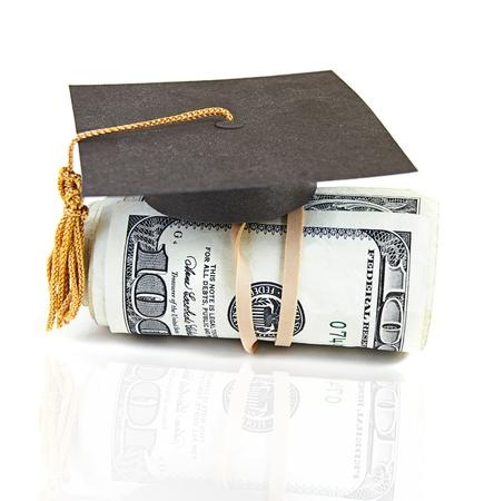 scholarship: mini graduation cap on rolled up cash