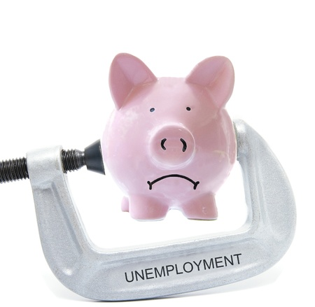 Sad piggy bank being squeezed in Unemployment vice, on white