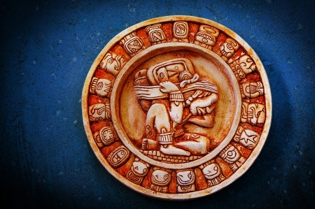 A carved Mayan calendar on textured background photo