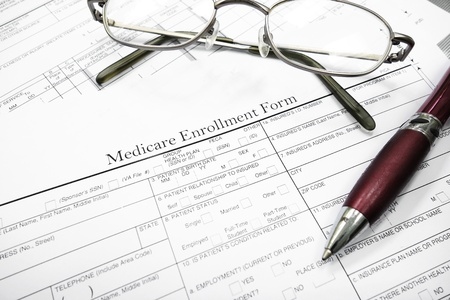 Medicare insurance form with glasses and pen                                photo