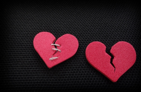 A pair of red broken hearts, one with threaded stitches