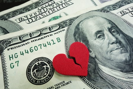 broken relationship: closeup of a broken red heart on cash - divorce concept