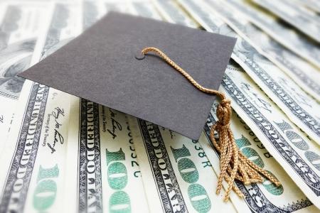 closeup of a mini graduation cap on cash                                Banco de Imagens