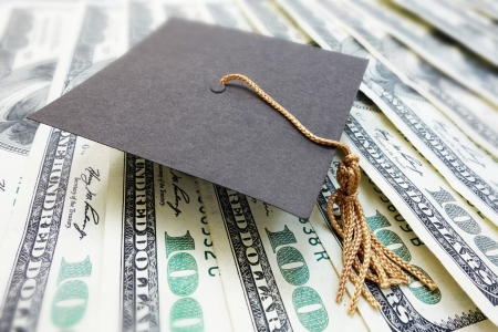 closeup of a mini graduation cap on cash                                Stock Photo - 23087572