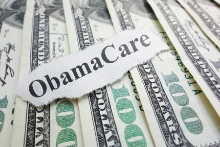 Closeup of an Obamacare newspaper headline on cash