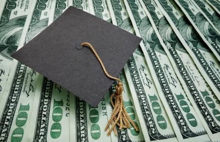 licenciatura: casquillo de la graduación en una variedad de billetes de cien dólares - concepto de educación Foto de archivo