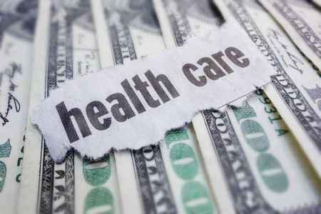 Closeup of health care newspaper headline, on cash