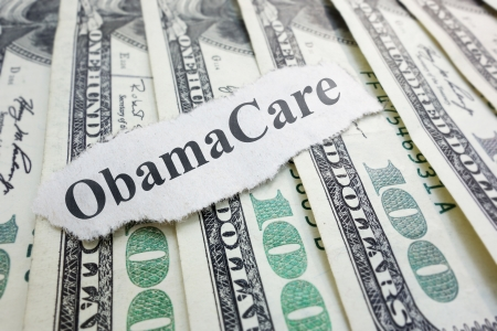 Closeup of an Obamacare newspaper headline on cash                               photo