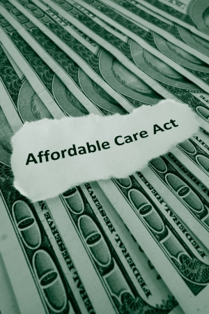 Closeup of Affordable Care Act, aka Obamacare text on money                                Stock Photo