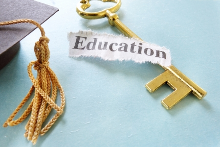 Education note on a golden key, with graduation cap