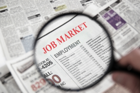 Magnifying glass over a newspaper classified section with Job Market text photo