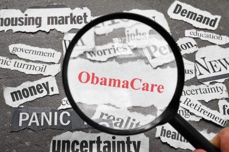 虫眼鏡と赤で ObamaCare の新聞の見出しを見て