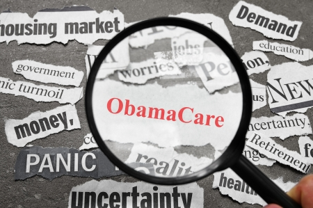Magnifying glass looking at newspaper headlines, with ObamaCare in red