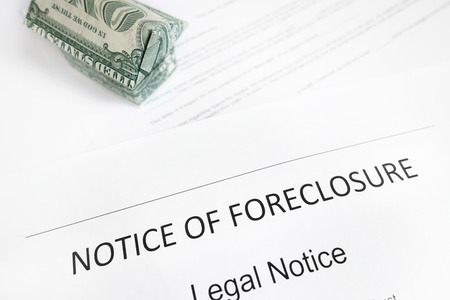 Home foreclosure document and origami dollar house                               Imagens