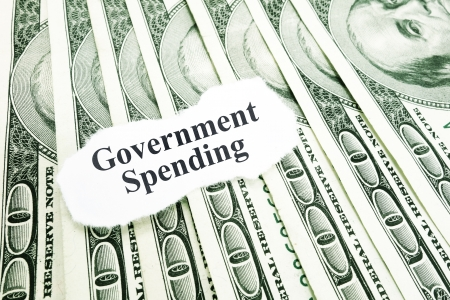 us government: Government Spending text on a paper scrap over money                                Stock Photo