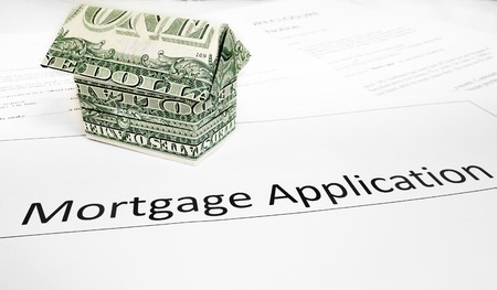 A mortgage application with an origami dollar house                                photo