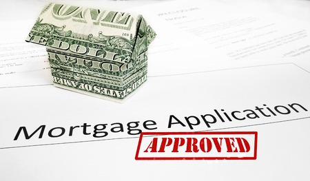 A mortgage application with an origami dollar house and Approval stamp                                photo