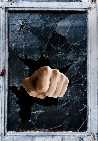 Fist punching through a shattered glass window                             photo
