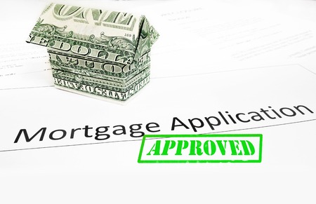 A mortgage application with an origami dollar house and Approval stamp                                Imagens