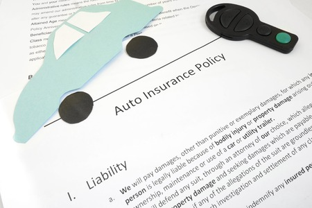 Auto insurance policy and key with paper car                                photo