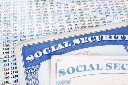 Tarjetas de Seguro Social y una hoja de números del presupuesto Foto de archivo - 26082952