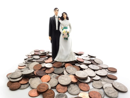 Plastic wedding couple on a pile of coins - money concept                                Фото со стока