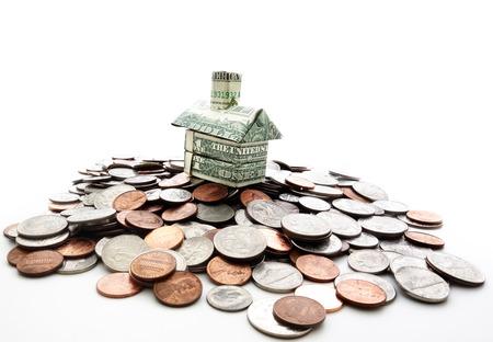 equidad: dinero de la casa en miniatura sobre una pila de monedas