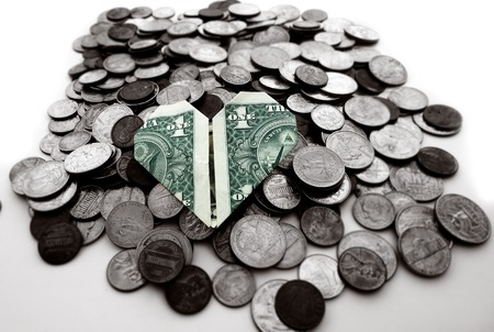 Origami heart shaped dollar on a pile of coins                                photo