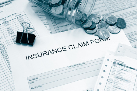 financial insurance: Assorted medical bills and a claim form with coins